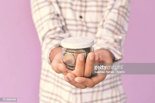 Midsection Of Boy Holding Container With Coins Against Wall
