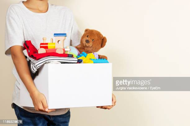 midsection of boy holding personal accessories in box against wall - mid section stock pictures, royalty-free photos & images