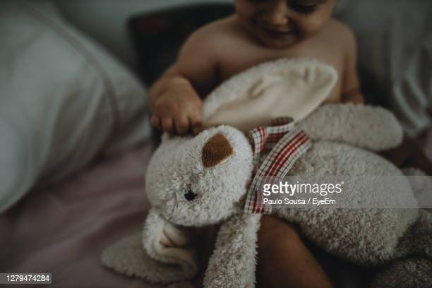 midsection of boy holding toy sitting on bed at home - one baby boy only stock pictures, royalty-free photos & images