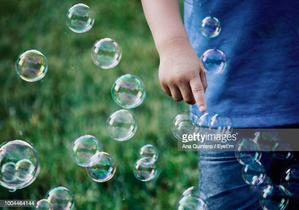 Midsection Of Boy Playing With Bubbles At Park