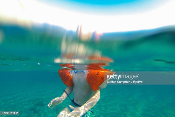 Midsection Of Boy With Water Wings Swimming In Sea