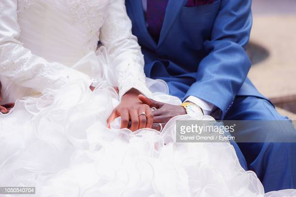 midsection of bridal couple sitting outdoors - wedding vows stock pictures, royalty-free photos & images