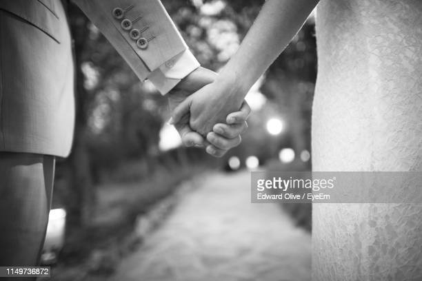 midsection of bride and bridegroom holding hands at wedding ceremony - marriage stock pictures, royalty-free photos & images