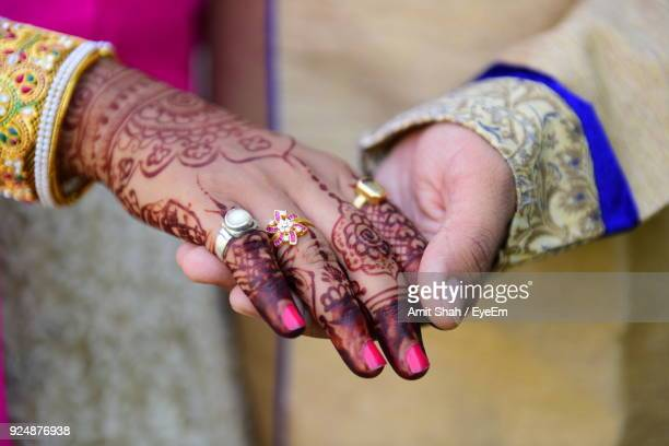 midsection of bride and bridegroom holding hands - heterosexual couple stock pictures, royalty-free photos & images