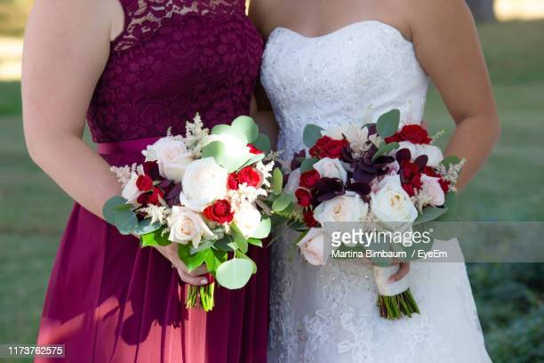 midsection of bride and bridesmaid holding rose bouquets while standing outdoors - bridesmaid stock pictures, royalty-free photos & images