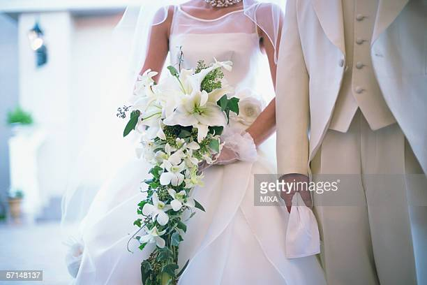 Midsection of bride and groom at wedding ceremony
