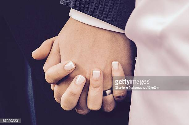 Midsection Of Bride And Groom Holding Hands During Wedding Ceremony