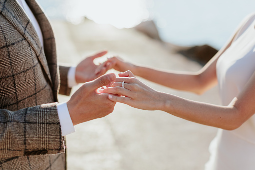 Midsection Of Bride And Groom Holding Hands While Standing Outdoors - gettyimageskorea