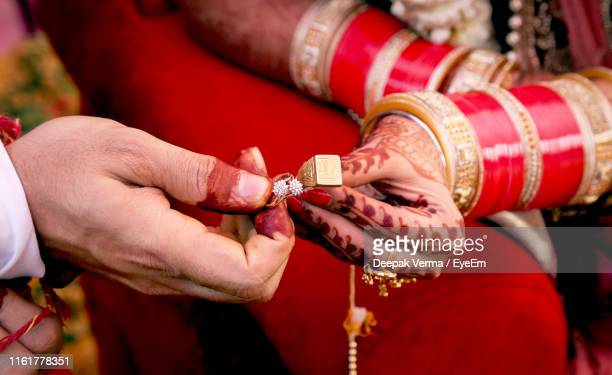 midsection of bride and groom holding rings during wedding ceremony - bangle stock pictures, royalty-free photos & images