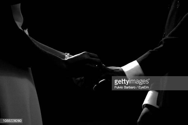 Midsection Of Bride And Groom Standing Against Black Background