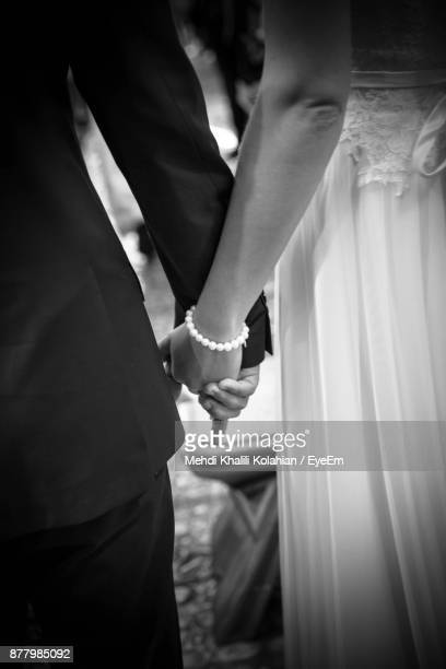 midsection of bride and groom with holding hands indoors - marriage stock pictures, royalty-free photos & images