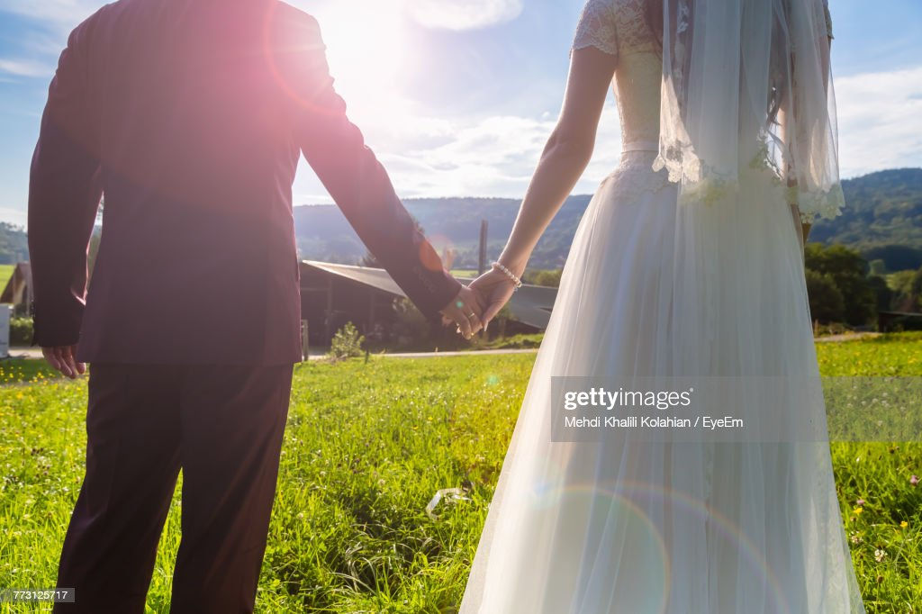 Midsection Of Bride And Groom With Holding Hands On Field Against Sky : Stock Photo