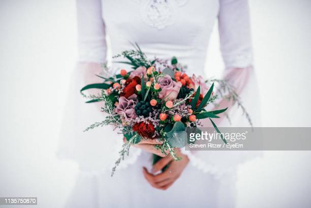 midsection of bride holding bouquet against white background - wedding dress stock pictures, royalty-free photos & images