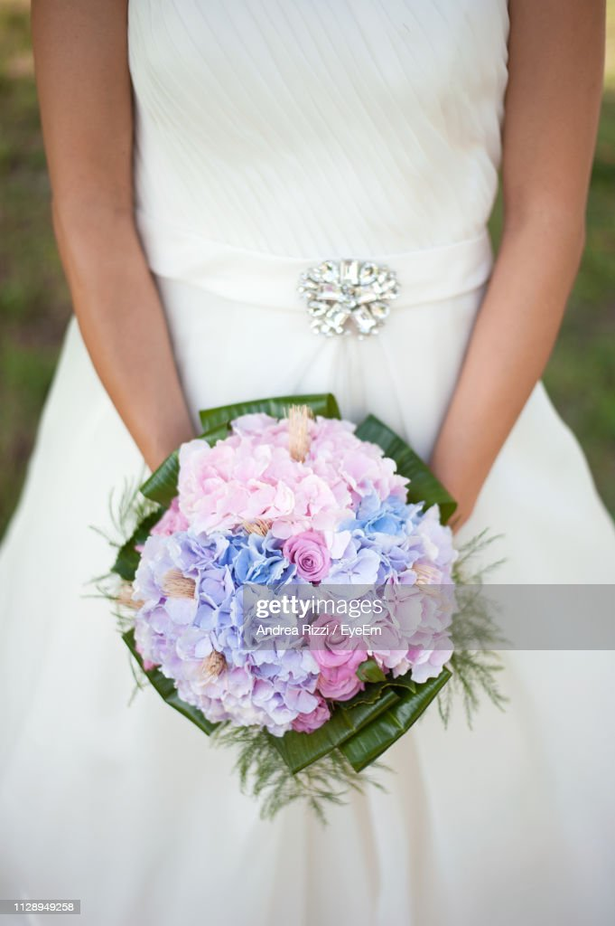 Midsection Of Bride Holding Bouquet Outdoors : Foto de stock