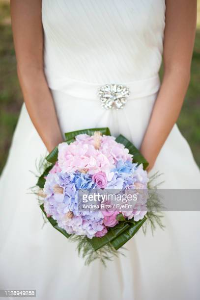 midsection of bride holding bouquet outdoors - andrea rizzi stockfoto's en -beelden