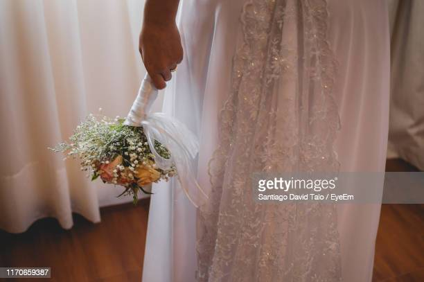 midsection of bride holding flower bouquet while standing at home - david ramos fotografías e imágenes de stock
