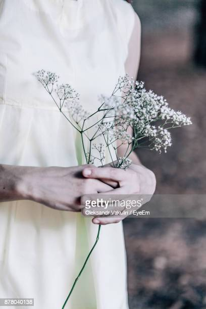 Midsection Of Bride Holding Flowers