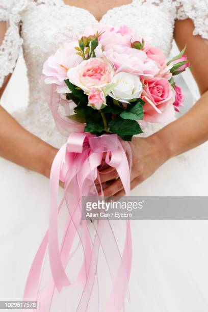 midsection of bride holding rose bouquet - pink dress stock pictures, royalty-free photos & images