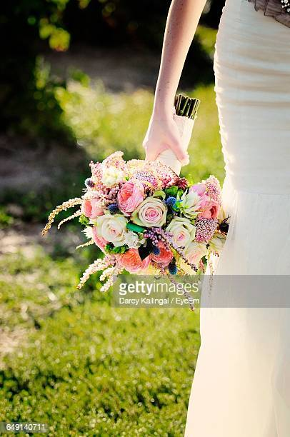 Midsection Of Bride Holding Wedding Bouquet