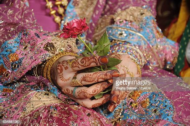 Midsection Of Bride In Sari Holding Rose