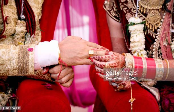 midsection of bride putting ring in groom finger during wedding ceremony - newlywed stock pictures, royalty-free photos & images