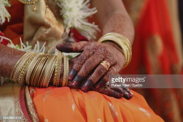 midsection of bride wearing sari while sitting in wedding ceremony - バングル ストックフォトと画像