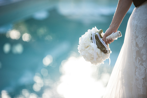 Midsection Of Bride Wearing Wedding Dress While Holding Bouquet By Swimming Pool - gettyimageskorea