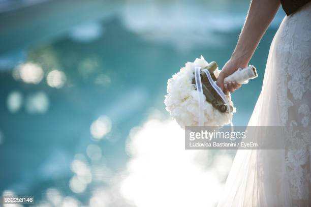Midsection Of Bride Wearing Wedding Dress While Holding Bouquet By Swimming Pool