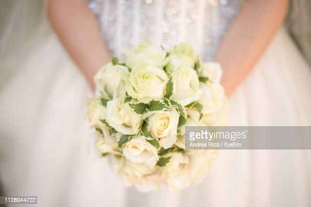 midsection of bride with bouquet in wedding ceremony - andrea rizzi stock pictures, royalty-free photos & images