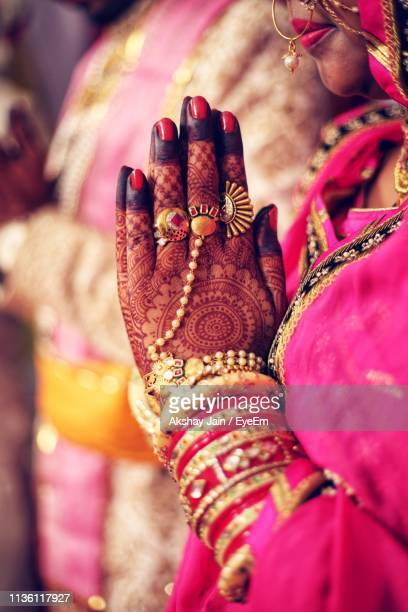 midsection of bride with bridegroom during wedding ceremony - indian wedding stock pictures, royalty-free photos & images