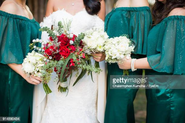 midsection of bride with bridesmaid holding bouquet - bridesmaid stock pictures, royalty-free photos & images