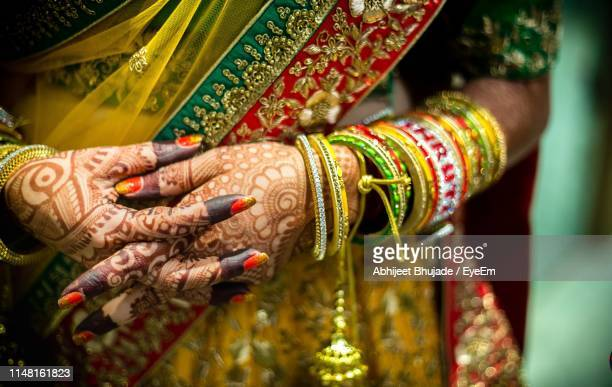 midsection of bride with hands clasped - mumbai stock-fotos und bilder