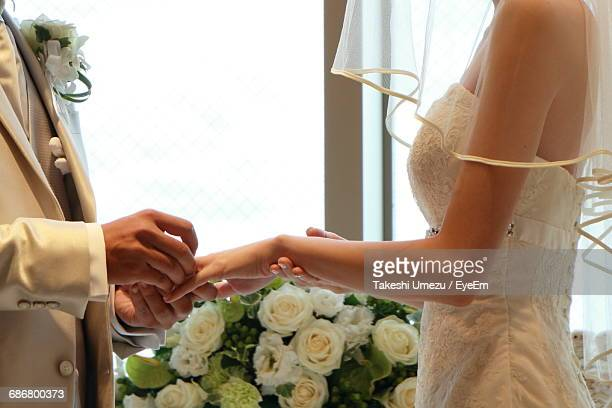 Midsection Of Bridegroom Putting Ring On Bride Finger During Wedding Ceremony