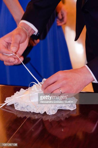 Midsection Of Bridegroom Removing Wedding Ring From Pillow On Table