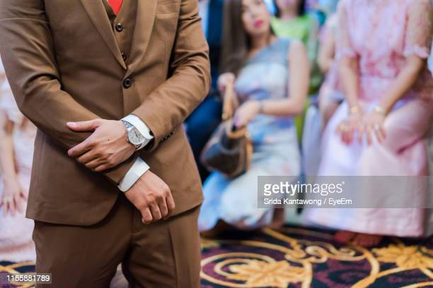 midsection of bridegroom standing at wedding ceremony - brown suit stock photos and pictures