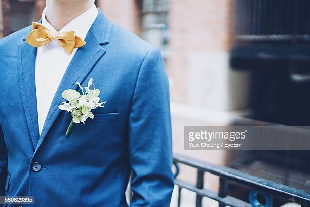 Midsection Of Bridegroom With Boutonniere On Suit Standing Against Building