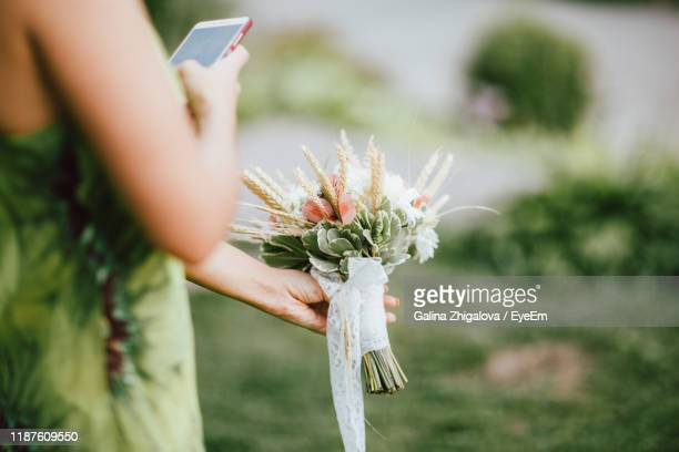 midsection of bridesmaid photographing while holding flower bouquet - bridesmaid stock pictures, royalty-free photos & images
