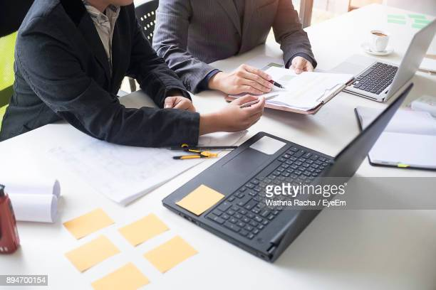 Midsection Of Business People Discussing By Laptop At Desk