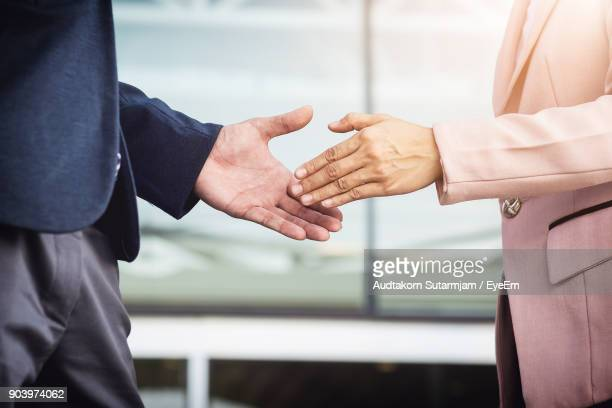 Midsection Of Business People Doing Handshake While Standing Outdoors