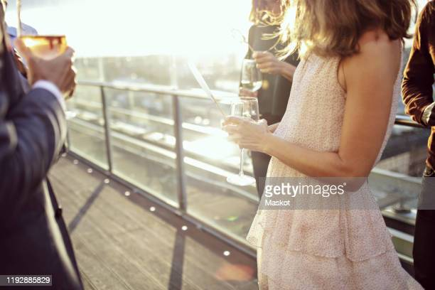 midsection of business people enjoying drinks after work on office terrace - vestirse formal fotografías e imágenes de stock