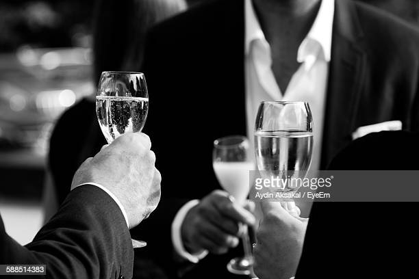 Midsection Of Business People Raising Toast