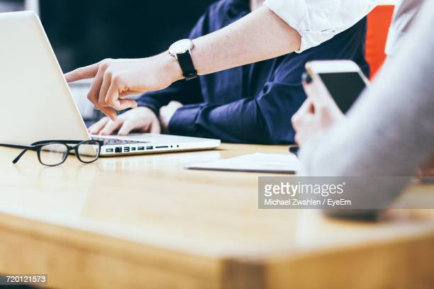 Midsection Of Business People Working At Table In Office