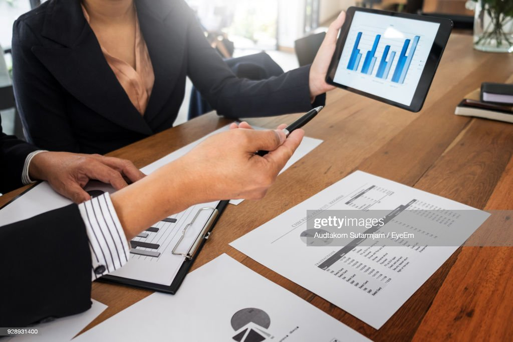 Midsection Of Business People Working On Digital Tablet At Office : Stock Photo