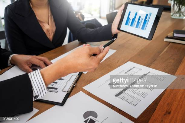 midsection of business people working on digital tablet at office - annual report stock pictures, royalty-free photos & images