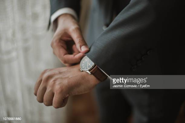 midsection of businessman adjusting sleeve - wrist watch stock pictures, royalty-free photos & images