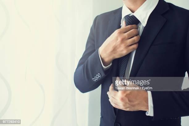 Midsection Of Businessman Adjusting Tie Against White Wall