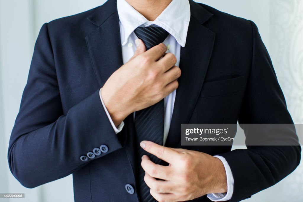 Midsection Of Businessman Adjusting Tie : Stock Photo