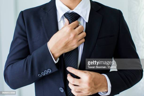 midsection of businessman adjusting tie - krawatte stock-fotos und bilder
