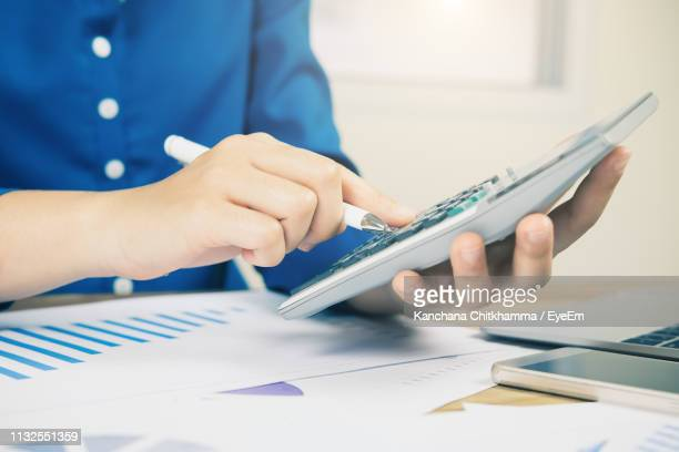 midsection of businessman analyzing data on desk in office - expense stock pictures, royalty-free photos & images