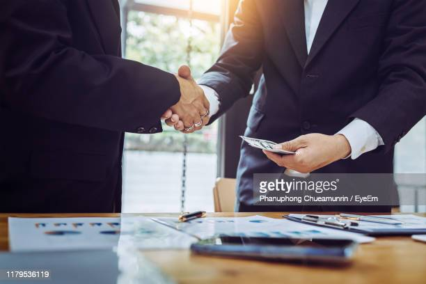 midsection of businessman bribing male colleague in office - corruption stock pictures, royalty-free photos & images